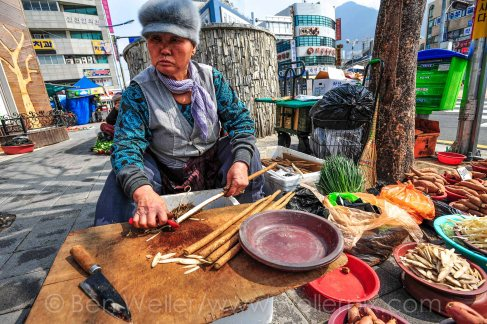 A woman slices roots at Gupo Market, a traditional market in Busan, South Korea.