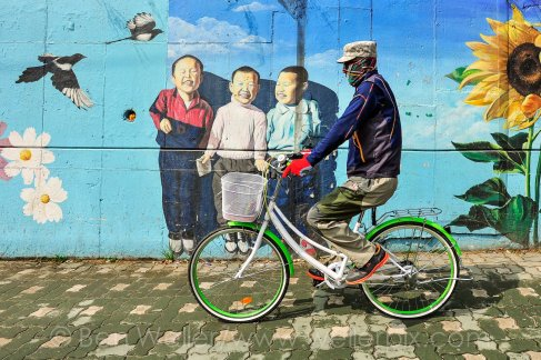 A man rides his bicycle past a mural near Gupo Market, a traditional market in Busan, South Korea.