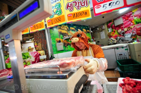 A butcher dressed in a cow costume weighs meat at his shop in Gupo Market, Busan, South Korea.