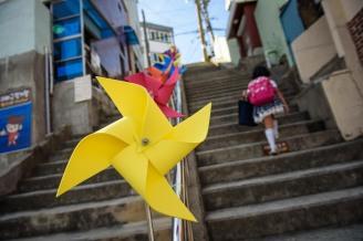 A girl walks past pinwheel street art on steps on Ibagu-gil in Busan, Korea.