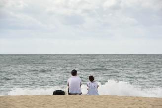 A couple watches the waves at Haeundae Beach, Busan, Korea.