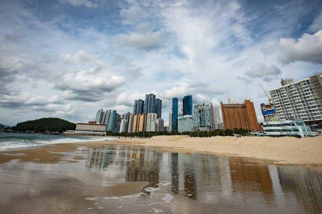 Buildings are reflected in a tidal pool at Haeundae Beach, Busan, Korea.