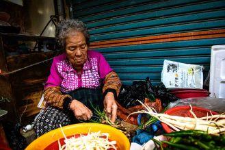 Old Korean woman preparing spring onions in Oncheon Market