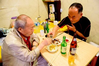 Two men share soju and beer in Oncheon Market in Busan