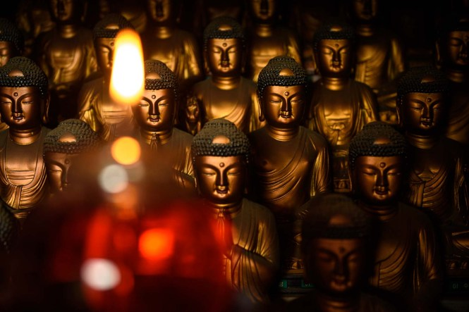 Candle and Buddha statues at Buddhist temple Seokbulsa
