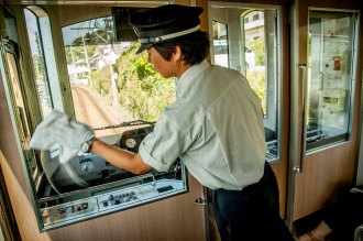 Enoden train conductor cleaning window in Kamakura, home of the 2020 Summer Japan Olympic sailing events