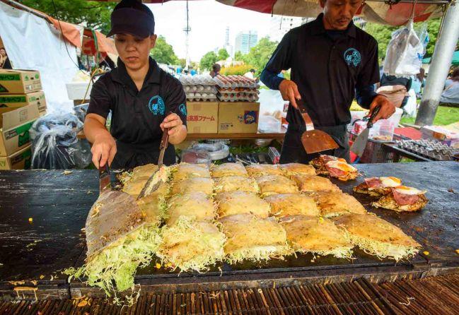 A man and women cook okonomiyaki at the Nagoya festival.