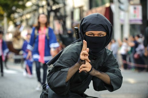 A man dressed in a ninja suit looks directly at the photographer during the Nagoya Festival parade.