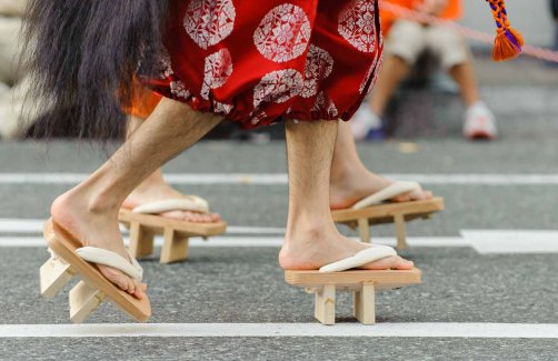 People wearing tall wooden sandals or geta during the parade at the Nagoya Festival.
