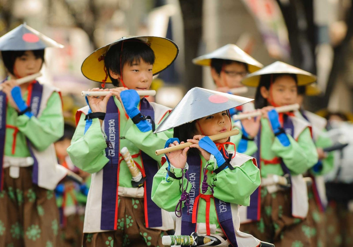 Children in traditional costumes play flutes during the Nagoya Festival.
