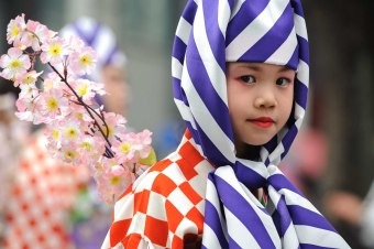 A girl wearing traditional Japanese clothes walks in a parade during the 2015 Nagoya Festival.