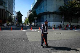 A traffic guard keeps the parade route clear.