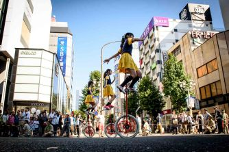 Women on tall unicycles ride during the parade at the Nagoya Festival in Nagoya, Japan.
