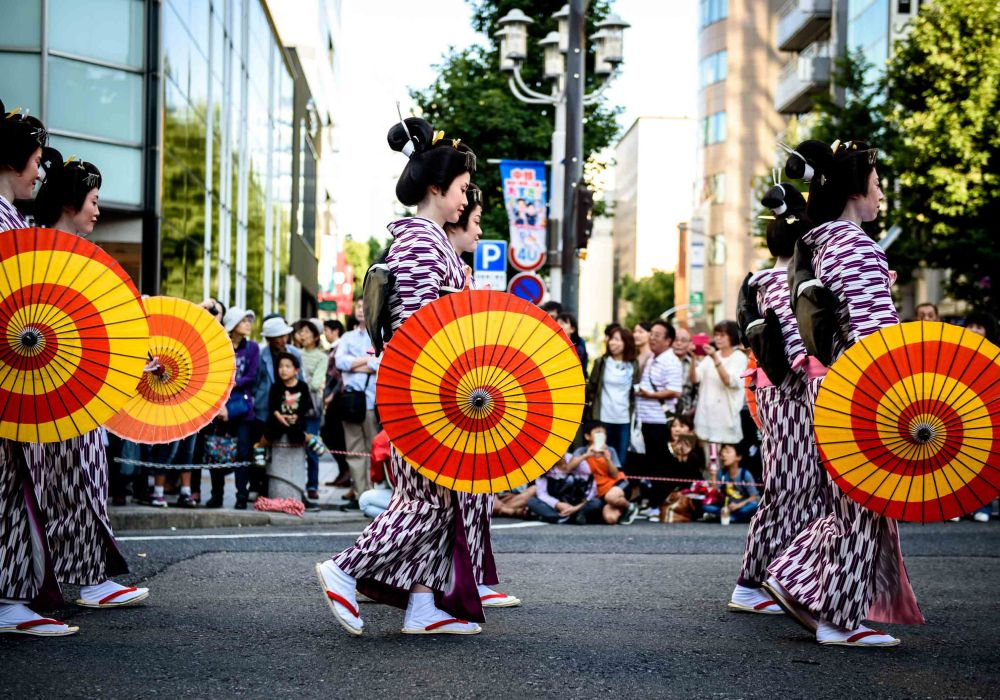Women wear traditional Japanese clothes walk with traditional umbrellas.