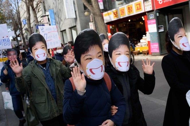 Protesters wear masks of Park Geun-hye