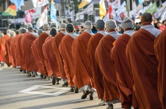 Buddhist monks walk in procession during an interfaith demonstration and vigil prior to protests in Seoul.