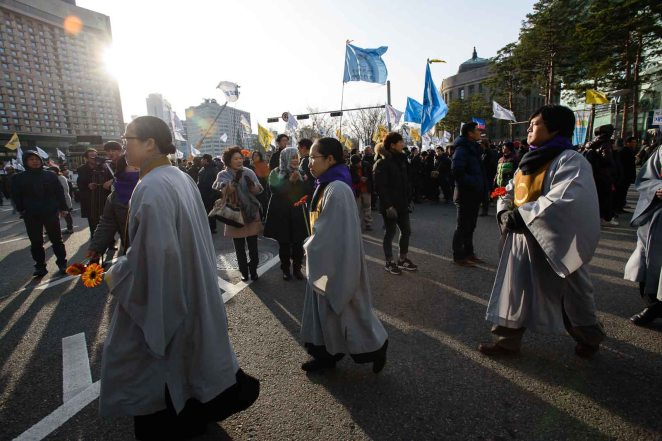 Christian leaders walk in procession during an interfaith demonstration and vigil prior to protests in Seoul.