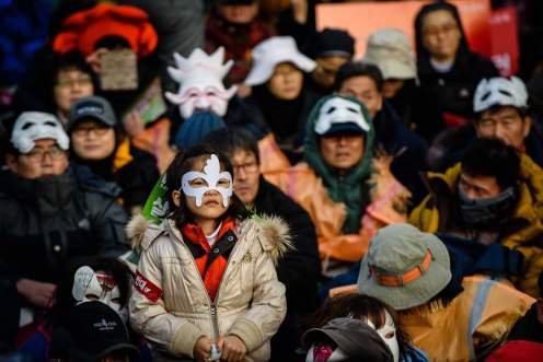 A young girl wears a mask among other protesters at Seoul Plaza.